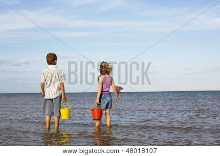 Rear view of a brother and sister with buckets and small fishnet enjoying the sea view