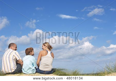 Rear view of parents and son sitting on sand and looking at eachother on beach