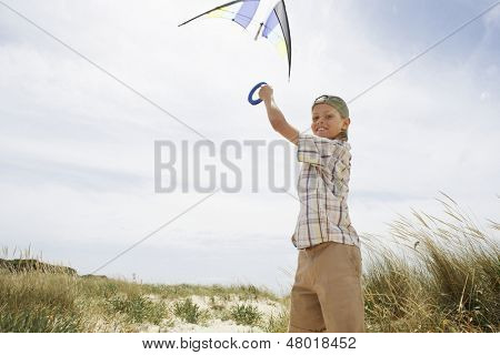 Side view portrait of preadolescent boy flying kite on a windy beach