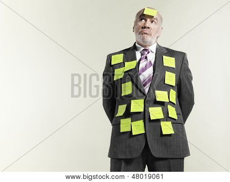 Mature businessman covered with sticky notes against gray background