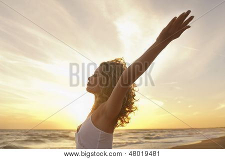 Side view of young woman with hands raised meditating at beach