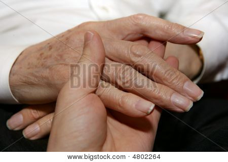 Verzorger hand in Senior's hand