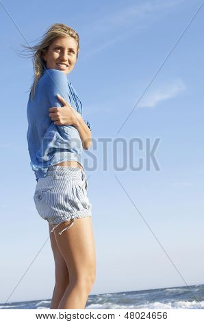 Low angle view of young woman with arms crossed standing against sky at beach