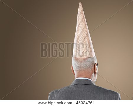 Closeup rear view of a middle aged businessman wearing dunce hat against brown background