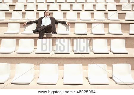 Middle aged businessman relaxing while sitting alone in center of empty auditorium outdoors