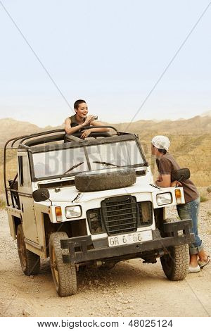 Young woman taking photograph of man standing by four-wheel-drive car