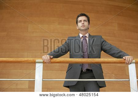 Low angle view of confident young businessman leaning on railing while standing against wooden wall