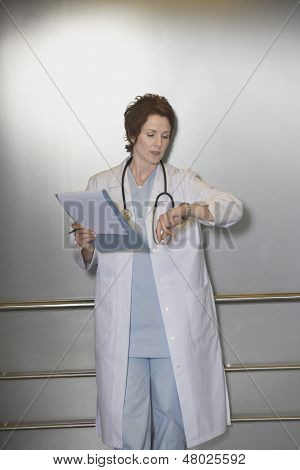 Female physician checking wristwatch in the elevator