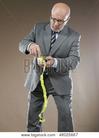 Middle aged businessman pealing an apple against brown background