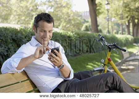 Happy young businessman using palmtop pilot while sitting on park bench