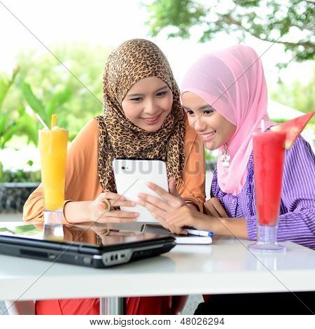 Two young pretty Asian muslim business woman in head scarf with book laptop