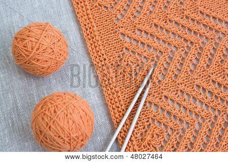 Orange balls, knitted pattern and knitting needles