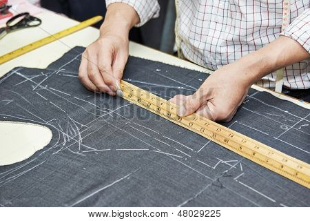 Tailor hands working with measure bar