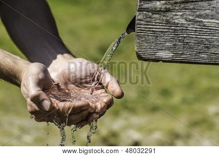 Thirsty Hands Taking Water From Well