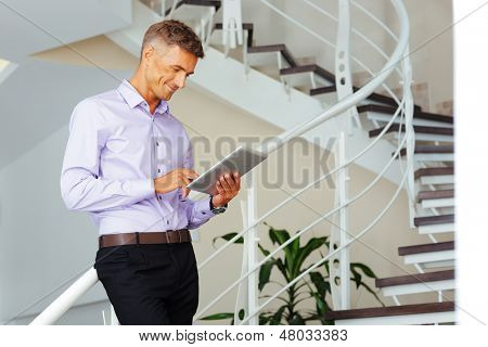 Happy mature businessman using his tablet