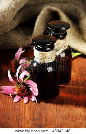 Medicine bottles with purple echinacea flowers on wooden table with burlap