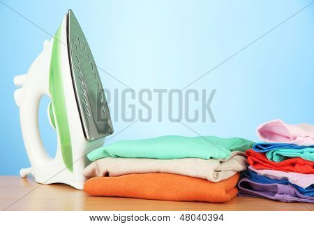 Steam iron with clothes, on color background