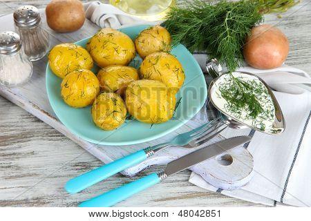 Boiled potatoes on platen on wooden board near napkin on wooden table