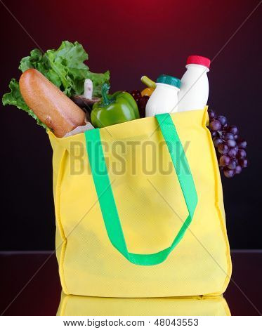 Eco bag with shopping on dark red background