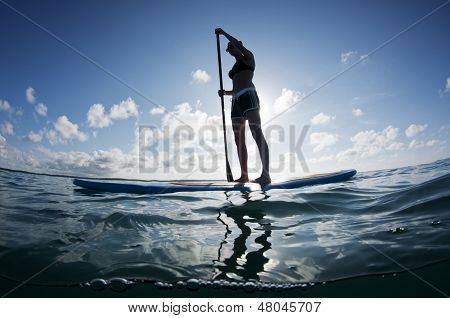 young female paddles a paddleboard off a Bahamian island