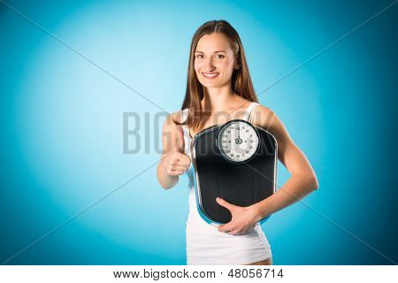 Diet and loosing weight, young woman with a scale, she is happy about the success