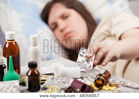 Adult woman patient hand holding vitamin pills lying down bed for cold and flu illness relief