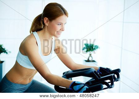 Portrait of young female training on simulator in gym