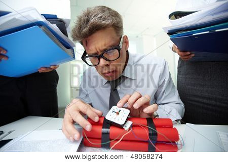 Mature accountant with dynamite being surrounded by colleagues with big heaps of papers