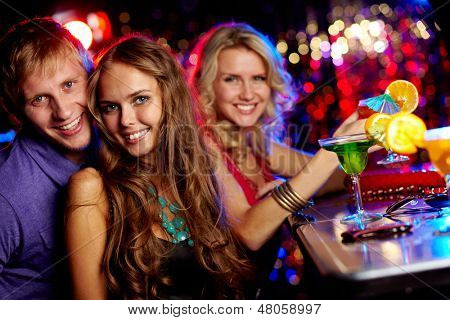 Image of happy couple looking at camera with pretty girl on background