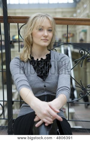 Young Attractive Blond Woman Sitting At Railing In State Department Store. Moscow
