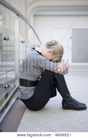 Young Attractive Sad Woman Sitting Put Head On Knees At Railing In State Department Store. Moscow