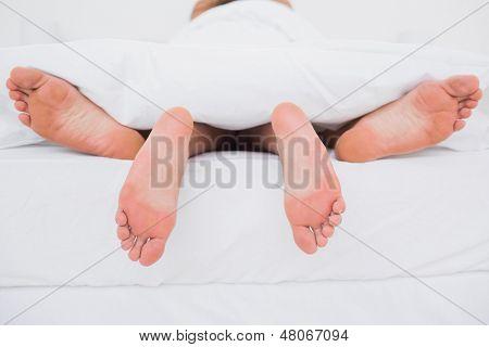 Vista traseira de um casal fazendo sexo na cama
