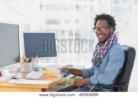 Smiling interior designer holding colour charts in a modern office