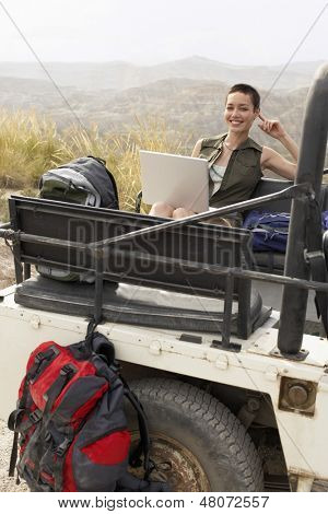 Portrait of young woman using laptop sitting in back of four-wheel-drive car in desert