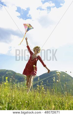 Low angle view of young woman flying kite against cloudy sky
