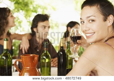 Portrait of happy young woman enjoying red wine with friends in background