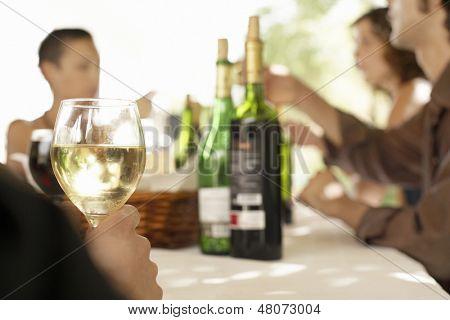 Vaso de vino blanco de mesa rodeada de gente de fiesta
