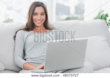 Portrait of a woman using her laptop sat on a couch