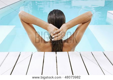 Rear view of young woman in swimming pool at poolside pulling back hair