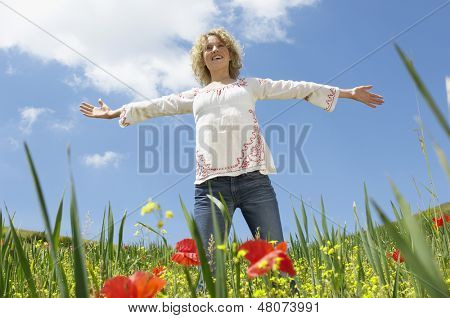 Low angle view of young woman with arms outstretched standing in poppy field