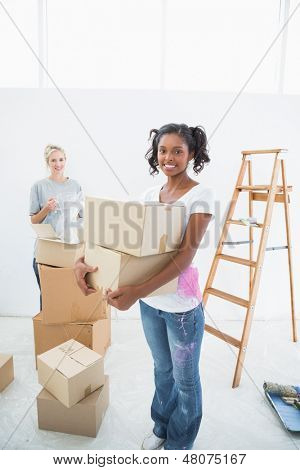 Young housemates moving into new home smiling at camera and unpacking boxes