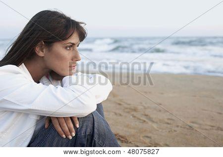Doordachte jonge vrouw op zoek weg met zee op achtergrond