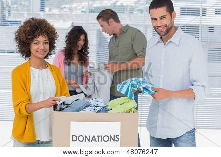 Team of volunteers taking out clothes from a donation box for a charity
