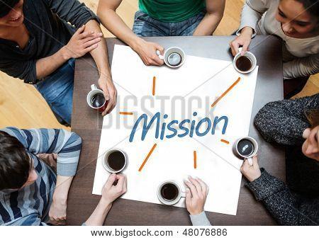 Team brainstorming über ein Poster auf einer Tabelle mit Mission darauf geschrieben