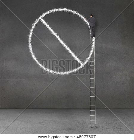 Businessman standing on a giant ladder and drawing forbidden sign on a grey wall