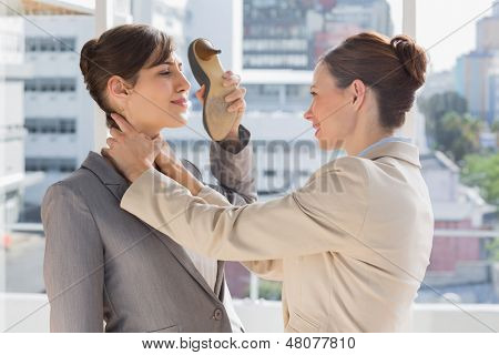 Businesswoman strangling another who is defending with her shoe in bright office
