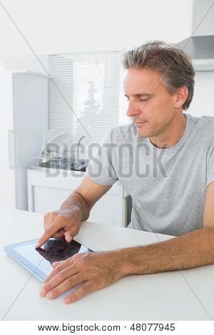 Smiling man using tablet pc in kitchen at home sitting at counter