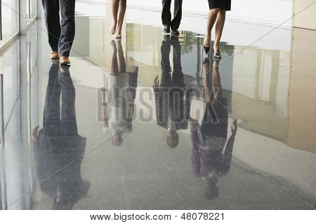 Low section of business people walking on marble flooring in office