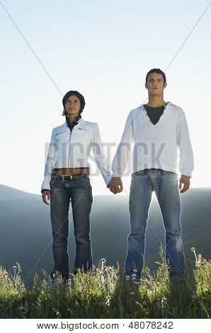 Confident multiethnic couple looking away while holding hands at park