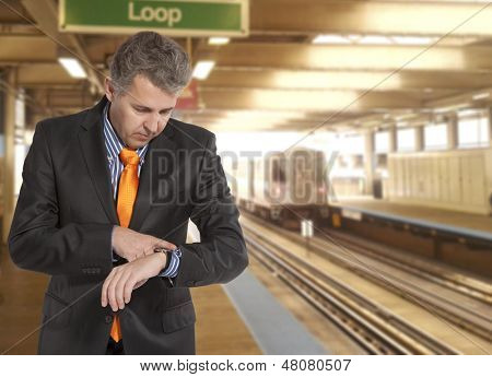 Train delay. Businessman looking at his watch